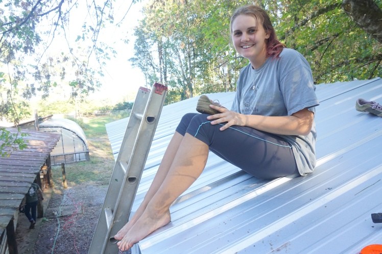 A smiling Alyssa after spending a couple hours screwing the metal roof onto the top of the house