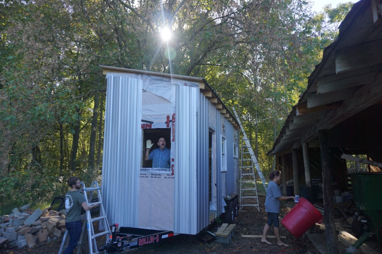 Berle standing inside our shining, splendid tiny house..