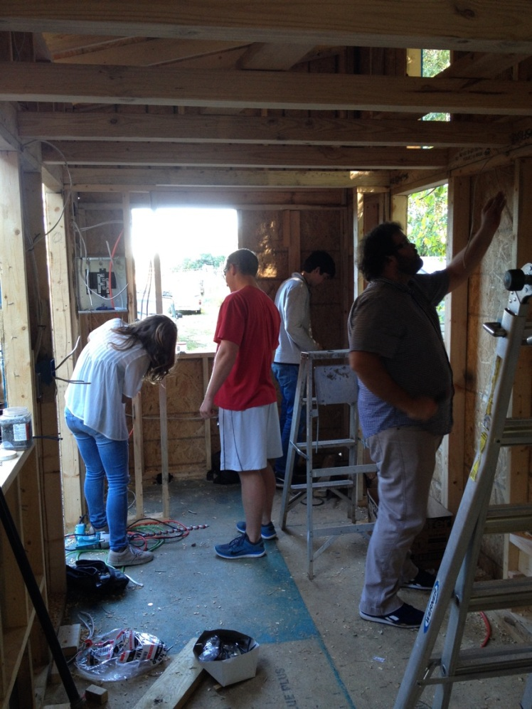All of us packed into our tiny house, working on the wiring.